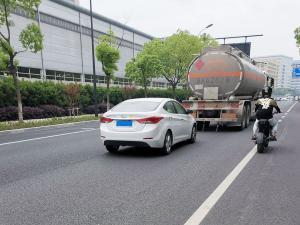 紧跟汽油危险品运输车的白色现代悦动(2张)