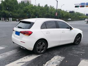 白色奔驰A级两厢车在路口转弯