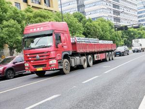 """车头印有""""中国重汽""""的红色卡车"""