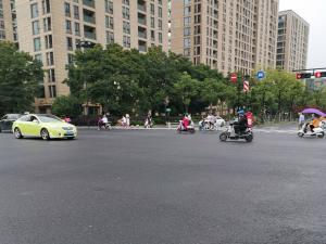 一辆绿色轿车通过红绿灯路口