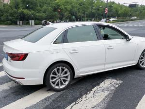 白色奥迪A4L轿车通过斑马线
