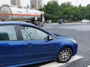 蓝色轿车和油罐车在过斑马线