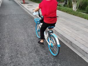 一辆共享单车的车头挂着口罩