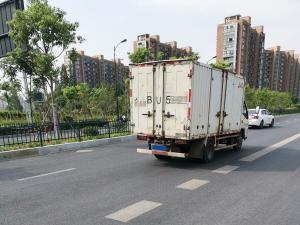 一辆白色箱式小货车 车尾贴着反光贴