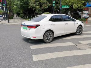 在斑马线上的丰田卡罗拉混动轿车