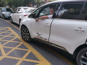 黄色网格线边白色汽车 开车车窗伸手吸烟
