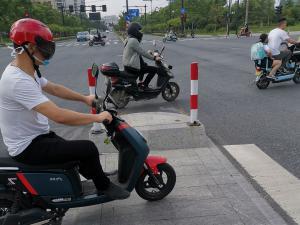 男子带红色头盔骑电动车
