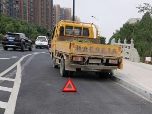 一辆货车在路边停车,后边放着三脚架