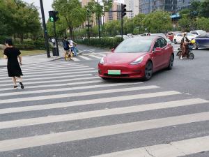 红色特斯拉转弯过人行道